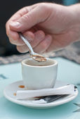 Hands with cup of coffee and spoon.Man stir sugar in cup of coffee. — Stock Photo