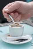 Mani con una tazza di caffè e spoon.man mescolare lo zucchero in una tazza di caffè. — Foto Stock