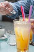 スプーンで、アイス キューブ、オレンジ ジュース .man という手でスプーンを保持している手します。 — ストック写真