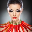 Beautiful young woman portrait with red hot and spicy peppers, fashion model with creative food vegetable make up looking side to empty copy space, isolated over black background. Red chili Paprika. — Stock Photo