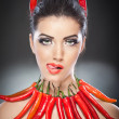 Beautiful young woman portrait with red hot and spicy peppers, fashion model with creative food vegetable make up looking side to empty copy space, isolated over black background. Red chili Paprika. - Stock Photo