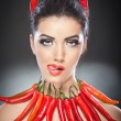 Beautiful young woman portrait with red hot and spicy peppers, fashion model with creative food vegetable make up looking side to empty copy space, isolated over black background. Red chili Paprika. — Stockfoto
