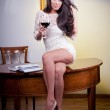 Sensual elegant young woman in white dress holding a wine glass.Young beautiful woman wearing a white short dress in the old hotel.Sensual elegant young woman in white dress looking forward — Stock Photo