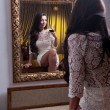 The beautiful girl in a short white dress looking into mirror. Young beautiful woman wearing a white short dress in the old hotel — Stock Photo #25363795
