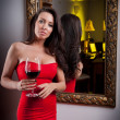 Royalty-Free Stock Photo: The beautiful girl in a long red dress posing in a vintage scene.Young beautiful woman wearing a red dress in the old hotel.Sensual elegant young woman in red dress looking into mirror