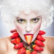 Creative makeup beauty shot of model with strawberries, artistic edit .Woman with strawberry necklace, wig and makeup professionally posing in studio.Beauty with strawberry. — Stock Photo #25751873