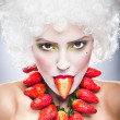 Creative makeup beauty shot of model with strawberries, artistic edit .Woman with strawberry necklace, wig and makeup professionally posing in studio.Beauty with strawberry. — Stock Photo