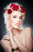 Hairstyle - beautiful sexy female art portrait with roses.Elegance. Genuine Natural Blonde Bride with red Flowers. Artistry.Portrait of a beautiful blonde woman with flowers in her hair. Fashion photo — Stock Photo