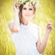 Young girl on golden wheat field.Portrait of beautiful blonde girl with wreath of wild flowers.Beautiful woman enjoying daisy field, pretty girl relaxing outdoor, harmony concept. — Stock Photo