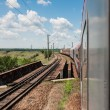 Railway goes to horizont in green and yellow landscape under blue sky with white clouds.railway under cloudy sky.Scenic railroad in rural area in summer and blue sky with white clouds. — Stock Photo
