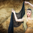 Stock Photo: Wombelly dancer with veil against rock beach. Dancing beautiful slim girl. Sexy arabiturkish oriental professional artist in yellow costume and diamond jewelry outdoor. exotic belly-dance star.