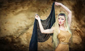 Woman belly dancer with veil against rock beach. Dancing beautiful slim girl. Sexy arabian turkish oriental professional artist in yellow costume and diamond jewelry outdoor. exotic belly-dance star. — Stock Photo