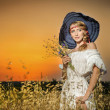 Young woman standing on a wheat field with sunrise on the background.Portrait of girl in field.Romantic young woman posing outdoor.Attractive woman in white dress in yellow wheat field at sunrise. — Photo
