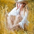 Fashion portrait woman with hat and white shirt sitting on a hay stack.very cute blond woman sitting down outdoor on the yellow grass with a hat — Stock Photo
