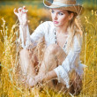 Fashion portrait woman with hat and white shirt sitting on a hay stack.very cute blond woman sitting down outdoor on the yellow grass with a hat — Stock Photo #27152325