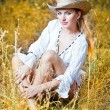 Fashion portrait woman with hat and white shirt sitting on a hay stack.very cute blond woman sitting down outdoor on the yellow grass with a hat — Stock Photo #27152337