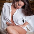 Young beautiful sexy woman in white shirt posing challenging indoor .Sexy brunette Woman with White men's shirt posing in vintage room .Attractive women sitting on old chair — Zdjęcie stockowe