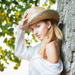 Fashion portrait woman with hat and white shirt sitting on a hay stack.very cute blond woman sitting down outdoor on the yellow grass with a hat — Stock Photo #27405705