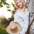 Fashion portrait woman with hat and white shirt sitting on a hay stack.very cute blond woman sitting down outdoor on the yellow grass with a hat — Stock Photo #27405715