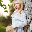 Fashion portrait woman with hat and white shirt sitting on a hay stack.very cute blond woman sitting down outdoor on the yellow grass with a hat — Stock Photo #27405719