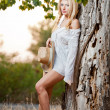 Fashion portrait woman with hat and white shirt sitting on a hay stack.very cute blond woman sitting down outdoor on the yellow grass with a hat — Stock Photo #27405729