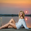 Beautiful girl with a white shirt on the pier at sunset.Sexy woman with long legs sitting on a pier .Color image of a beauty girl sitting on a pier, overlooking a lake — Stock Photo