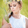 Young girl with wreath on golden wheat field.Portrait of beautiful blonde girl with wreath of wild flowers.Beautiful woman enjoying daisy field, pretty girl relaxing outdoor, harmony concept — Stock Photo #27421563