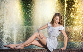 Attractive girl in white short dress sitting on parapet near the fountain in the summer hottest day.Girl with dress partly wet playing with water.Portrait of beautiful blonde women near the fountain — Stock Photo