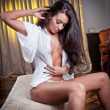 Young beautiful sexy woman in white shirt posing challenging indoor in vintage room.Sexy brunette Woman with White men's shirt in hotel room — Foto Stock