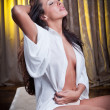 Stock Photo: Young beautiful sexy woman in white shirt posing challenging indoor in vintage room.Sexy brunette Woman with White men's shirt in hotel room