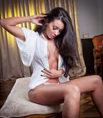 Young beautiful sexy woman in white shirt posing challenging indoor in vintage room.Sexy brunette Woman with White men's shirt in hotel room — Stock Photo