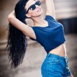 Portrait of a beautiful sexy woman with denim shorts and sunglasses in urban background . Attractive female brunette woman posing in blue jeans short in urban scene .Young woman in blue jeans short — Stock Photo #27635531