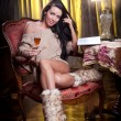 Beautiful sexy woman with glass of wine reading a book sitting on chair. Portrait of a woman with long legs posing challenging Sexy woman sitting in wood chair and reading in a vintage scene — Stock Photo #27637121