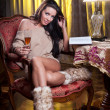 Beautiful sexy woman with glass of wine reading a book sitting on chair. Portrait of a woman with long legs posing challenging Sexy woman sitting in wood chair and reading in a vintage scene — Stock Photo #27637123
