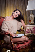 Beautiful sexy woman with glass of wine reading a book sitting on chair. Portrait of a woman with long legs posing challenging Sexy woman sitting in wood chair and reading in a vintage scene — Stock Photo