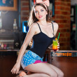 Attractive smiling pinup woman in denim shorts sitting on bar stool and drinking lemonade. — Stock Photo