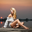 Beautiful girl with a white shirt on the pier at sunset.Sexy woman with long legs sitting on a pier .Color image of a beauty girl sitting on a pier, overlooking a lake — Stock Photo #28160219