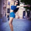 Portrait of a beautiful sexy woman with denim shorts and sunglasses in urban background . Attractive female brunette woman posing in blue jeans short in urban scene .Young woman in blue jeans short — Stock Photo #28296791