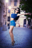 Portrait of a beautiful sexy woman with denim shorts and sunglasses in urban background . Attractive female brunette woman posing in blue jeans short in urban scene .Young woman in blue jeans short — Stock Photo