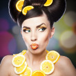 Beautiful girl with slices lemon as neck less.Portrait of a woman with oranges as a accessories. Fashion model with creative food vegetable make-up .Sensual woman with luxury makeup and hair style — Stock Photo #28350687