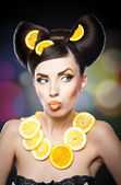 Beautiful girl with slices lemon as neck less.Portrait of a woman with oranges as a accessories. Fashion model with creative food vegetable make-up .Sensual woman with luxury makeup and hair style — Stock Photo