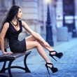 Handsome attractive girl wearing short skirt and high heels standing outside in urban scene.Fashion model in blue short skirt with long sexy legs on the street .Woman sitting on bench in the city — Stock Photo