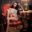 Beautiful sexy woman sitting on chair and relaxing. Portrait of a woman with long legs posing challenging Sexy woman sitting in wood chair and reading in a vintage scene — Stock Photo #28651041