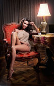 Beautiful sexy woman sitting on chair and relaxing. Portrait of a woman with long legs posing challenging Sexy woman sitting in wood chair and reading in a vintage scene — Stock Photo