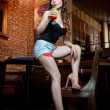 Attractive smiling pinup woman in denim shorts sitting on bar stool and drinking lemonade. Gorgeous Pinup model with white bow on her head and black bra drinking and posing in vintage bar — Stock Photo