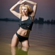 Attractive blonde woman in water at sunset .Beautiful swimsuit model.The beautiful sensual bikini model posing against a setting sun on a body of water .Erotic art photo — Stock Photo #29186583