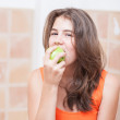 Pretty teen girl eating apple, indoor.Beautiful teenage girl biting an apple .Picture of beautiful teenage biting a green apple — Stock Photo #29229997