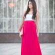Full length of young caucasian female with long red skirt standing in front of a fountain in a summer day — Stock Photo #29281239