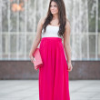 Full length of young caucasian female with long red skirt standing in front of a fountain in a summer day — Stock Photo #29281249