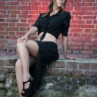 Charming young brunette woman in black dress and high heels near the brick wall.Sexy gorgeous young woman near old wall.Full length portrait of a cute woman with long hair near a brick wall — Stock Photo